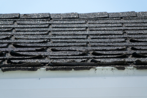 Damaged black roof shingles